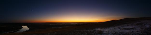 Panoramisch uitzicht op de rivier vanaf de heuvel. avondlucht na zonsondergang.