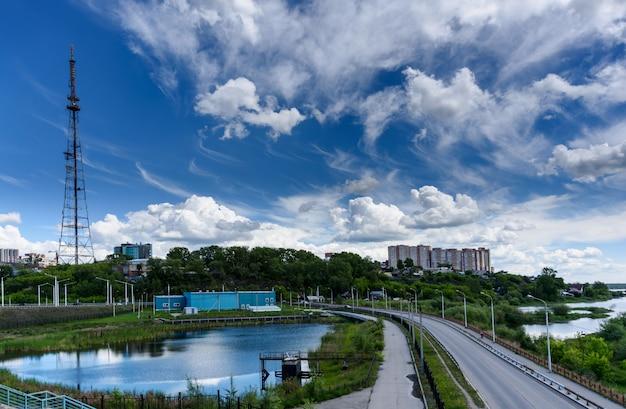 Panoramisch uitzicht op de stad irkoetsk, kleine vijver met reflectie, tv-toren en weg van de academische brug in zonnige zomerdag met prachtige wolken