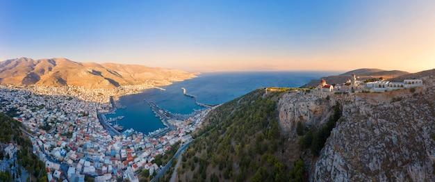 Panoramisch uitzicht op de stad pothia, de hoofdstad van kalymnos, griekenland, en het klooster van agios savvas op de top van de heuvel, aan de linkerkant