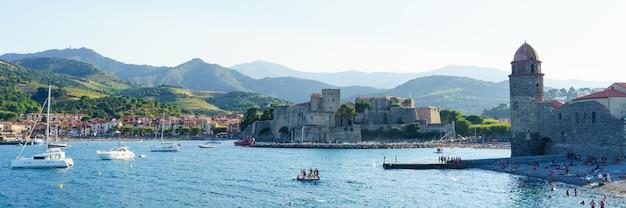 Panoramisch uitzicht op de toren van het kasteel in een middeleeuwse haven met boten en mensen op het strand. reis concept