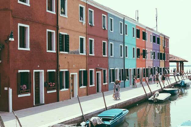 Panoramisch uitzicht op felgekleurde huizen en waterkanaal met boten in burano, het is een eiland in de venetiaanse lagune. zomer zonnige dag en blauwe lucht