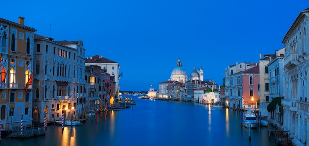 Panoramisch uitzicht op het canal grande en de basiliek santa maria della salute 's nachts