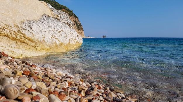 Panoramisch uitzicht op kiezelstrand met helder azuurblauw water en gelaagde rotsen