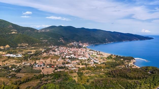 Panoramisch uitzicht op stratonion vanaf de drone, meerdere gebouwen aan de egeïsche zee kosten, heuvels bedekt met weelderig groen, griekenland