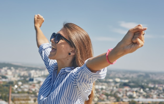 Panoramisch uitzicht over een stad en een jonge vrouw in een goed humeur op de voorgrond met haar armen gebald