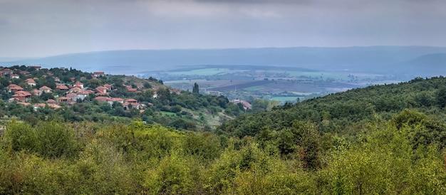 Panoramisch uitzicht over landelijk bulgaars dorp en bergen in de oppervlakte.