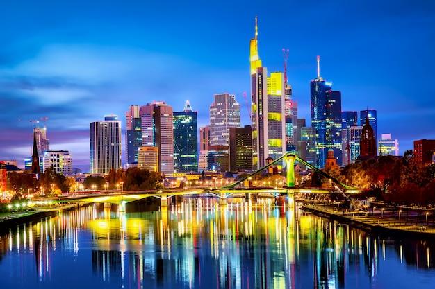 Panoramisch uitzicht stadsgezicht skyline van zakenwijk met wolkenkrabbers en spiegelreflecties in de rivier de main tijdens zonsondergang blauwe uur, frankfurt am main. hessen, duitsland.