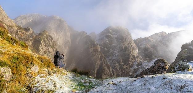 Panoramisch van een fotograaf die een foto maakt met het statief in de besneeuwde winterzonsondergang, op de berg van peñas de aya in de stad oiartzun nabij san sebastian, spanje