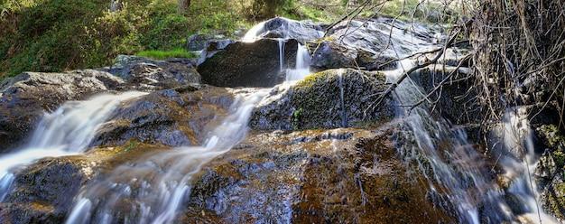 Panoramisch van waterval van water dat van de rotsen in het betoverde bos valt