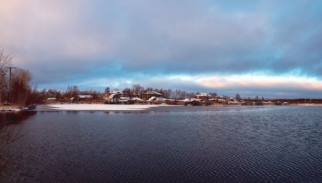 Panoramisch winters aanblik met oude huizen in de buurt van een besneeuwd meer. authentieke noordelijke stad kem in de winter. rusland.