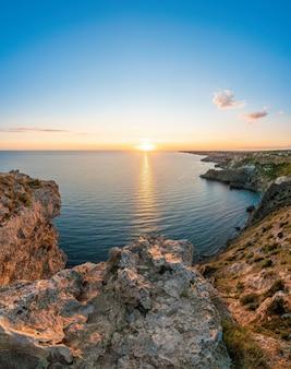 Panoramisch zeegezicht uitzicht op rotsachtige kust kalme azuurblauwe zee en heldere zonsondergang