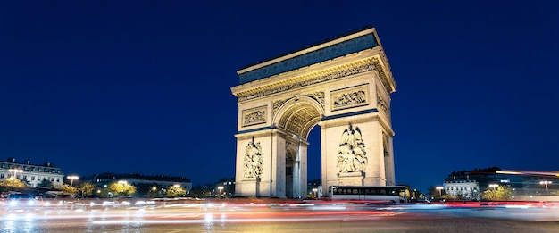 Panoramisch zicht op arc de triomphe 's nachts xith autolichten