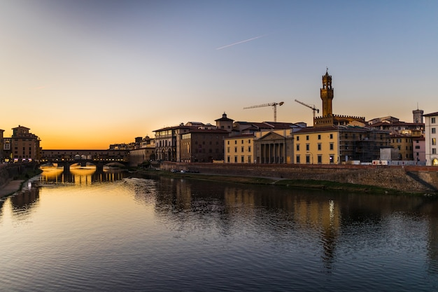Panoramisch zicht op de beroemde ponte vecchio met rivier de arno bij zonsondergang in florence, italië