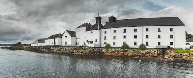 Panoramisch zicht op de gebouwen van de laphroaig-distilleerderij islay island, schotland, grijze bewolkte hemel vóór de