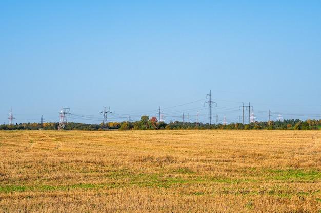 Panoramisch zicht op de hoogspanningslijn en de zendmasten die in een rij aan de horizon in het herfstveld staan
