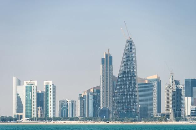 Panoramisch zicht op de moderne skyline van doha door het blauwe water. concept van rijkdom en luxe.