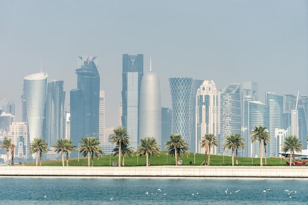 Panoramisch zicht op de moderne skyline van doha met palms voorgrond