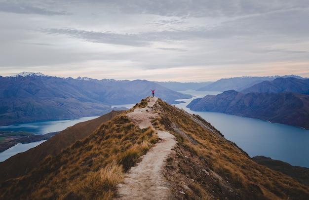 Panoramisch zicht op de roys peak in nieuw-zeeland met lage bergen in de verte onder cloudscape