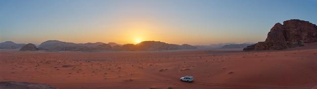 Panoramisch zicht op de zonsondergang in de woestijn van wadi rum, jordanië. de zon gaat onder achter de bergen terwijl een jeep het uitzicht in zich opneemt.