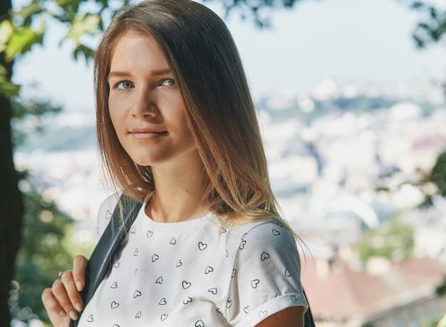 Panoramisch zicht op een stad en een jonge vrouw op de voorgrond