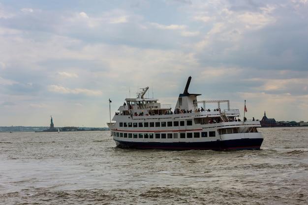Panoramisch zicht op jacht dat passagiers vervoert op de hudson-rivier in de buurt van statue of liberty new york