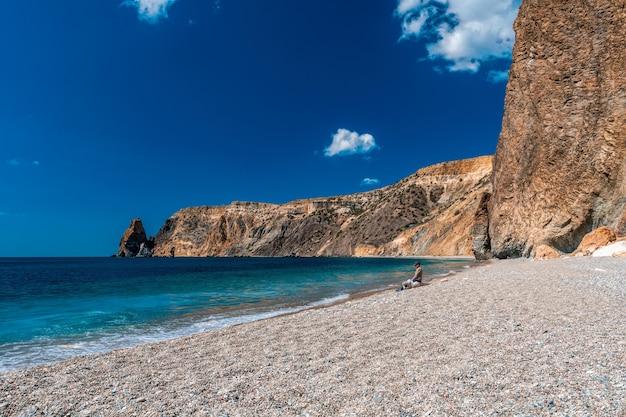 Panoramisch zicht op leeg kiezelstrand met helder azuurblauw water en gelaagde rotsen, jasper beach, fiolent, balaklava, stad sevastopol op de krim. het concept van rust, stilte en eenheid met de natuur.
