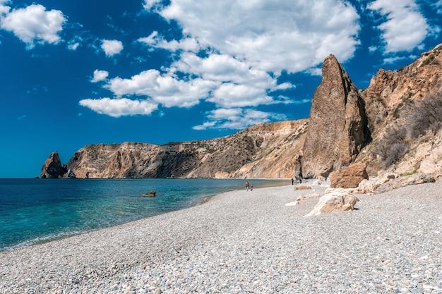 Panoramisch zicht op leeg kiezelstrand met helder azuurblauw water en rotsen