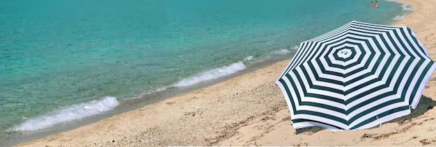 Panoramisch zicht op parasol op het strand met blauwe turquoise zee