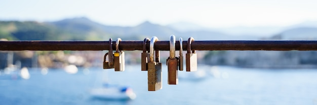 Panoramisch zicht op roestige sloten op een reling aan de kust in een zonnige dag