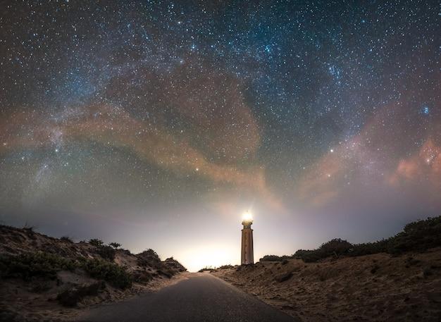 Panoramisch zicht op vuurtoren met de boog van de melkweg