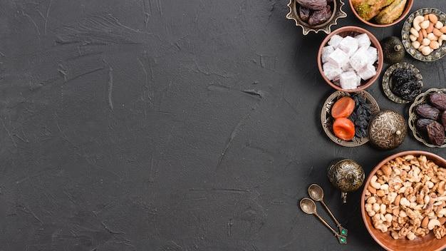 Panoramisch zicht op witte lukum; noten en gedroogde vruchten voor ramadan festival op zwarte concrete achtergrond