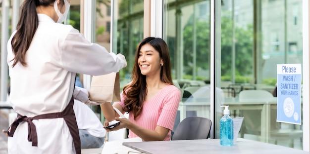 Panoramisch zicht van aantrekkelijke vrouw vrouwelijke klant nemen afhaalmaaltijden tas bestellen van serveerster dragen gezichtsmasker. afhaal of afhaal foodserviceconcept in een nieuw normaal na coronavirus-pandemie.