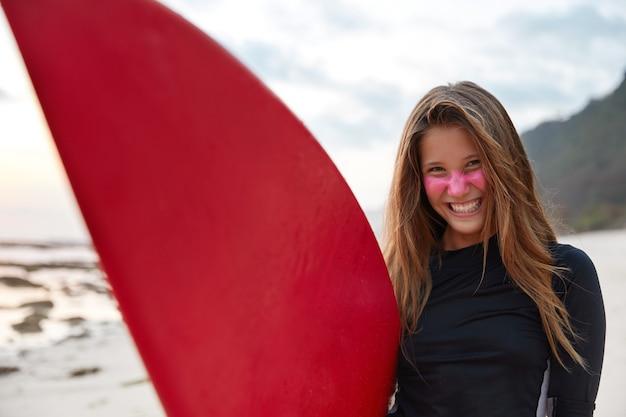 Panoramisch zicht van blij lachende aantrekkelijke surfer heeft roze zinkcrème op het gezicht aangebracht voor bescherming tegen zonnestralen