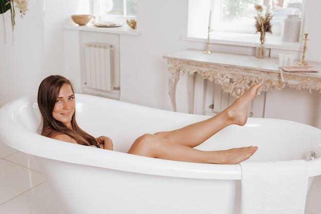 Panoramisch zicht van gelukkig en dromerig jong volwassen meisje dat een bad neemt, tijd doorbrengt in de badkamer, ochtendroutine procedure maakt en breed lacht