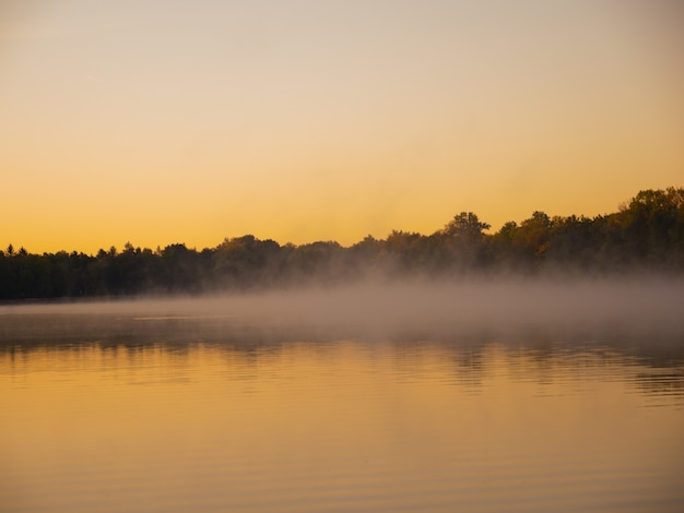 Panoramisch zicht van mist zittend op het oppervlak van het water tijdens schemering