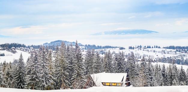 Panoramisch zicht van oude traditionele boerderij zittend op de top van een heuvel in schilderachtige winter wonderland landschap wolken