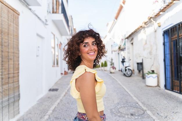 Panoramisch zicht van vrouw op vakantie in spanje. wit spaans kustconcept. gelukkige vrouw reizen.