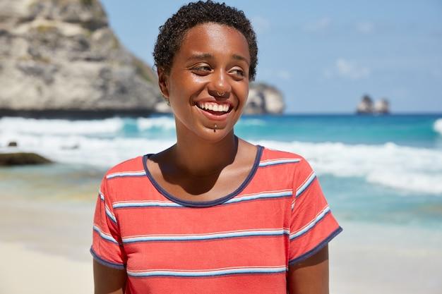 Panoramisch zicht van zwarte meid hipster heeft een brede glimlach