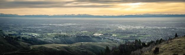 Panoramisch zonsondergangschot van stad met bergsportheuvels christchurch nieuw-zeeland