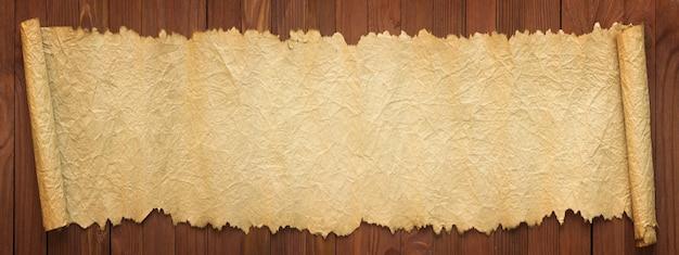 Panoramische achtergrond van oud papier. uitgevouwen rol op tafel