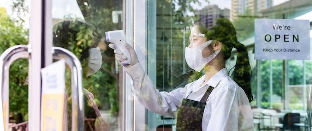 Panoramische aziatische serveerster met gezichtsmasker die temperatuur aan klant neemt alvorens in restaurant te komen. nieuw normaal restaurantlevensstijlconcept na coronavirus covid-19 pandemie.