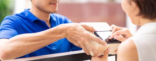Panoramische aziatische vrouw ondertekent elektronische handtekening naar draagbaar mobiel apparaat na ontvangstpakket