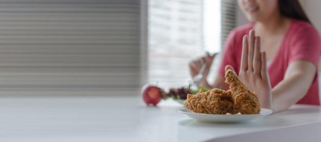 Panoramische banner. dieet. jonge mooie vrouw weigert gebakken kip, junkfood of ongezond voedsel en het eten van verse groentesalade voor een goede gezondheid thuis