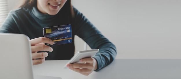 Panoramische banner. jonge vrouw invoeren van beveiligingscode met mobiele slimme telefoon en creditcard betalen op het bureau thuis kantoor