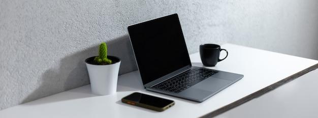 Panoramische banner van werkplek met laptop, smartphone, koffiemok en cactus op wit bureau.