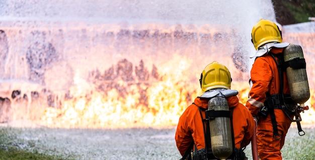 Panoramische brandweerman die een brandblusser van chemisch schuim gebruikt om te vechten met de vlam van een olietanker