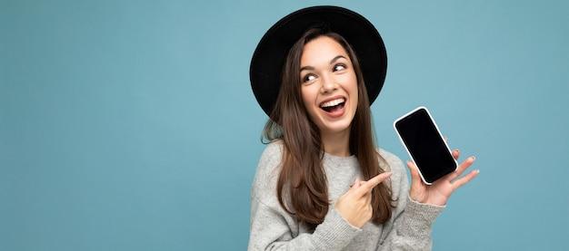 Panoramische close-up van charmante jonge gelukkige vrouw, gekleed in zwarte hoed en grijze trui met telefoon