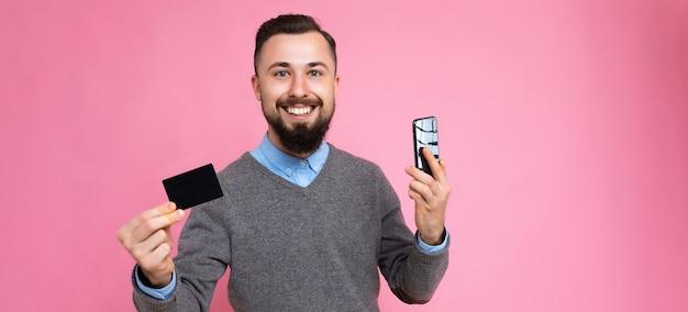 Panoramische foto shot van knappe lachende brunette bebaarde jonge man dragen stijlvolle grijze trui en blauw shirt geïsoleerd over achtergrond muur met creditcard en mobiele telefoon camera kijken.