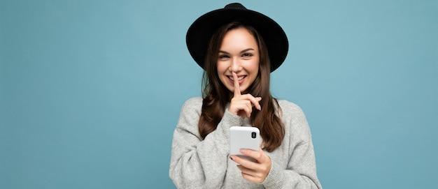 Panoramische foto van aantrekkelijke jonge glimlachende vrouw die zwarte hoed en grijze sweater draagt