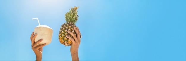 Panoramische foto van handen met fruit in tropisch paradijs over hemel